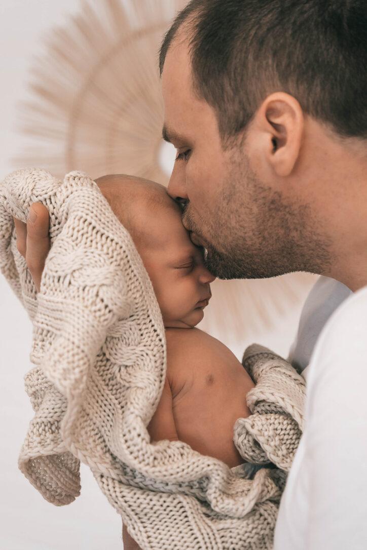 Papa und sein kleiner Sohn in Liebe anhand der Babyfotografie für immer festgehalten