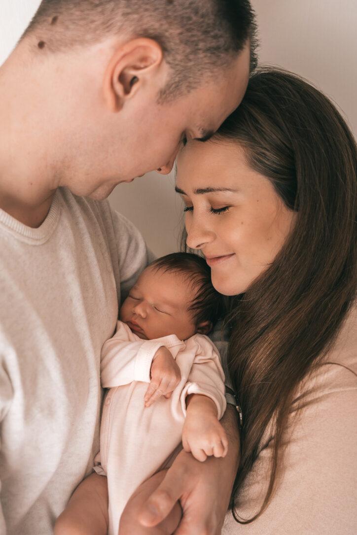 Ein emotionales Bild von den Eltern mit ihrem Baby bei einem Fotoshooting in Bad Säckingen - Selina Denz, deine Fotografin für liebevolle und natürliche Babyshootings in Lörrach und Rheinfelden - Newbornfotografin Selina Denz